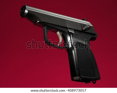 semi-automatic hand gun on red background, loaded position - stock photo