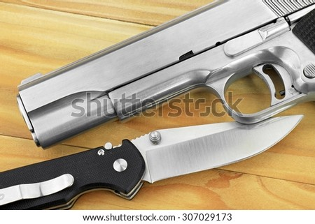 Semi-automatic handgun and tactical knife on wooden background, .45 pistol. - stock photo