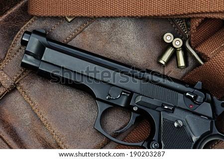 Semi-automatic handgun lying over a Leather handbag, 9mm pistol, Close-up - stock photo