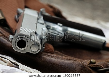 Semi-automatic handgun lying over a Leather handbag, .45 pistol, Close-up Barrel. - stock photo