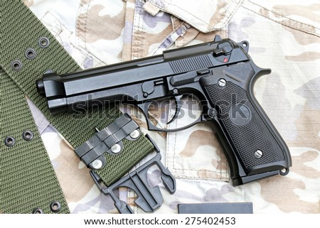 Semi-automatic handgun on camouflage background, Gun on Military texture, 9mm pistol.  - stock photo