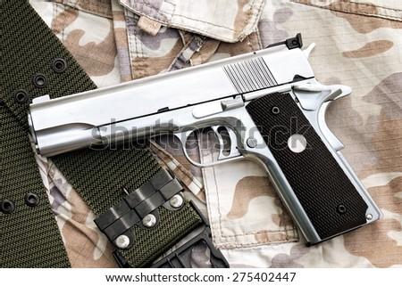 Semi-automatic handgun on camouflage background, Gun on Military texture, .45 pistol. (Color Process) - stock photo