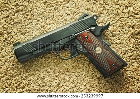 Semi-automatic handgun on carpet background, .45 pistol, 1911 model. Process HDR detail. - stock photo
