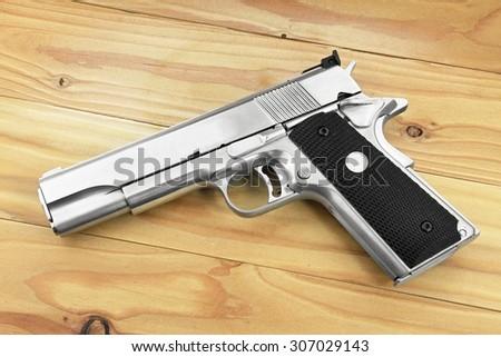 Semi-automatic handgun on grey wooden background, .45 pistol. Guns. - stock photo