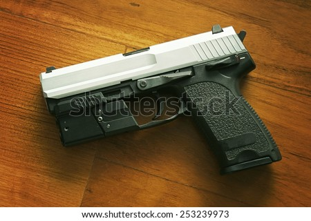 Semi-automatic handgun on wooden background, 9mm pistol. Process HDR detail. - stock photo