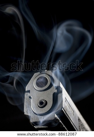 Semi-automatic handgun that is enveloped in smoke after a shot was taken - stock photo