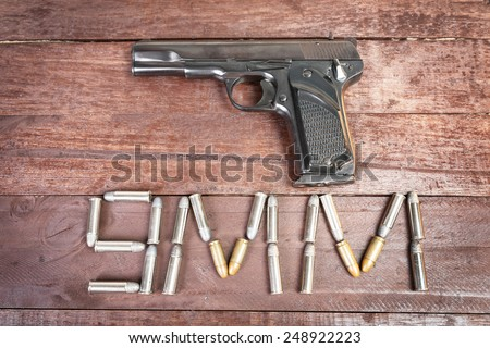 Semi-automatic 9mm gun isolated on wooden background. - stock photo