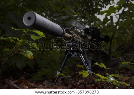 Semi automatic rifle with a suppressor in some dark trees - stock photo