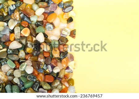 Semi precious jewelery stones closeup on a golden paper background - stock photo