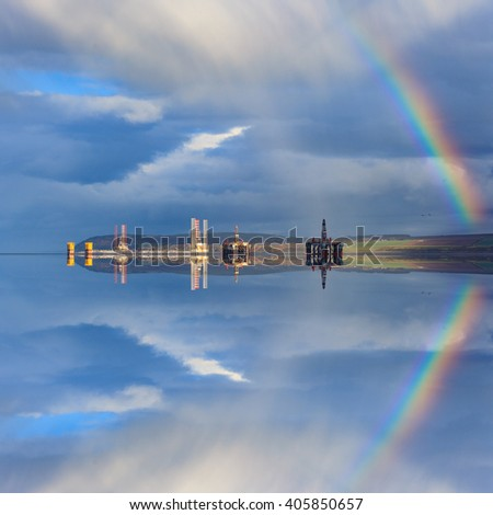 Semi Submersible Oil Rigs and Rainbow with Reflection at Cromarty Firth in Invergordon, Scotland - stock photo