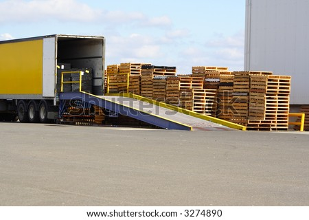 Semi truck backed onto loading ramp and stack of pallets - stock photo