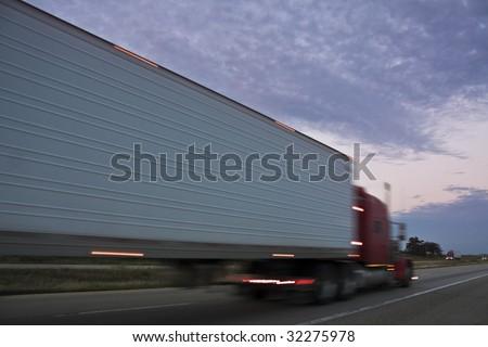 Semi Truck driving at sunset - stock photo