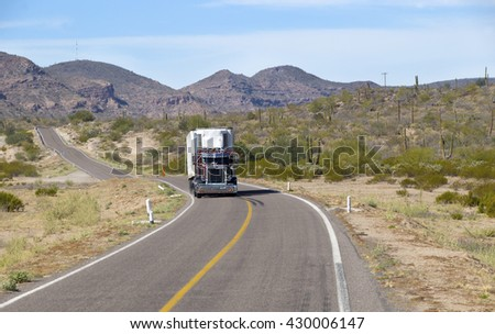 SEMI TRUCK DRIVING ON HIGHWAY, USA - MARCH 16, 2016: Semi truck going fast on the desert mountain highway  - stock photo