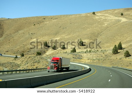 Semi truck going fast on interstate highway - stock photo