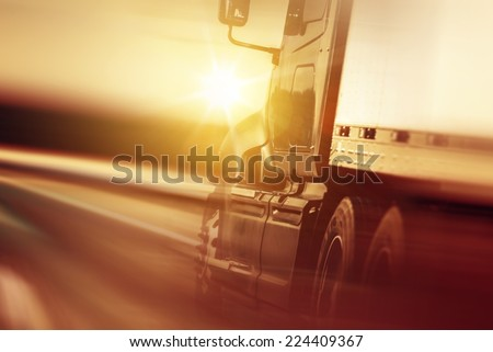 Semi Truck In Motion. Speeding Truck on the Highway. Trucking Business Concept - stock photo
