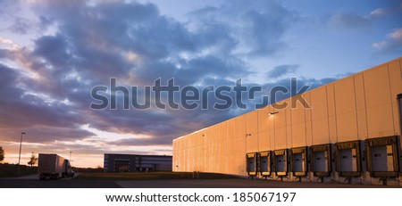 Semi Truck leaving the warehouse during the sunset.  - stock photo
