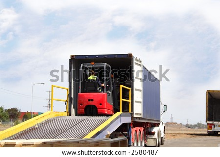 Semi truck with forklift driver on loading ramp - stock photo