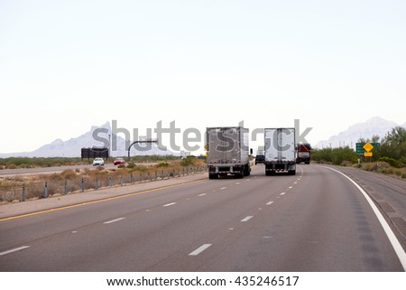 Semi Trucks with different trailers carrying commercial goods on flat Arizona multilane road with poor vegetation and sculpted mountains. Back view. - stock photo