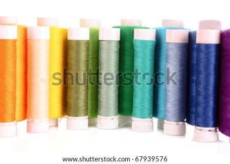 Semicircle of many-coloured bobbins of thread isolated on white - stock photo