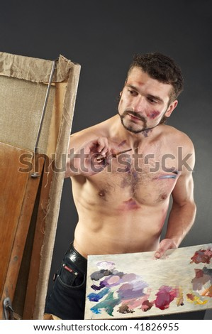 Seminude artist paints on an easel - stock photo