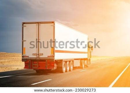 semitruck driving to sunset - stock photo