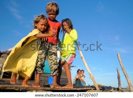 SEMPORNA, MALAYSIA - JULY 5 : Unidentified Sea Bajau's kids play on their stilt house on July 5, 2009 in Sabah, Malaysia. Children here do not attend school for lack of means and resources. - stock photo