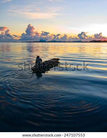 SEMPORNA, MALAYSIA - JULY 3 : Unidentified Sea Bajau's man rowing a boat July 3, 2009 in Sabah, Malaysia. The Sea Gypsies are sea nomads that move from one place to another. - stock photo