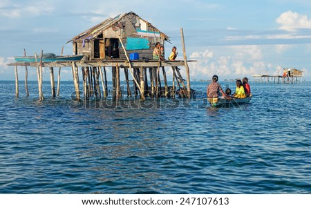 SEMPORNA, MALAYSIA - JULY 5 : Unidentified Sea Bajau's people rowing a boat on July 5, 2009 in Sabah, Malaysia. The Sea Gypsies are sea nomads that move from one place to another. - stock photo