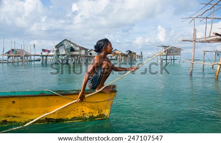 SEMPORNA, MALAYSIA - MAY 10 : Unidentified Sea Bajau's children rowing a boat on May 10, 2009 in Sabah, Malaysia. Children here do not attend school for lack of means and resources. - stock photo