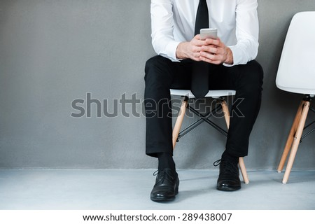 Sending business message. Close-up of young man in shirt and tie holding mobile phone while sitting on chair against grey background - stock photo