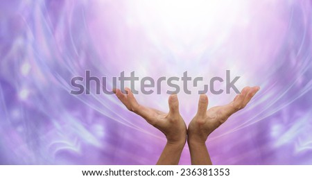 Sending Distant Healing into the Light  -   Female hands outstretched sending healing into the light above on an ethereal purple energy formation background - stock photo