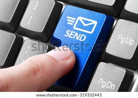 Sending email. gesture of finger pressing send button on a computer keyboard - stock photo