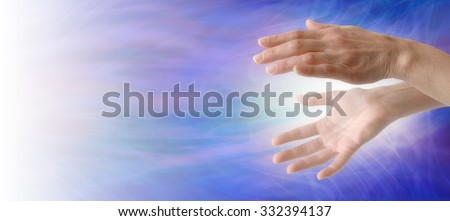 Sending Healing Energy  - Pair of female hand with energy between sending towards the light on left hand side, on a blue energy formation background with plenty of copy space  - stock photo