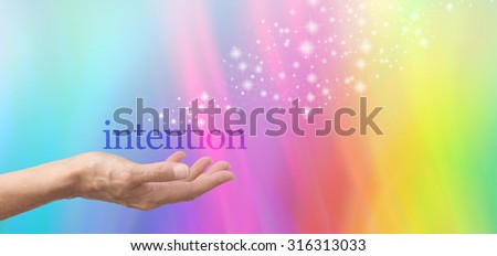 Sending out Good Intentions - female hand palm up with the word INTENTION floating above, on a rainbow colored graduated background with a stream of random sparkles  - stock photo