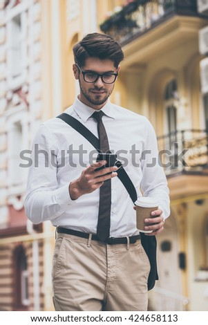 Sending quick message. Confident young man in glasses holding coffee cup and using his smart phone while walking outdoors - stock photo