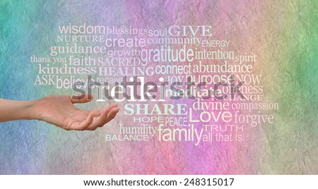 Sending Reiki Healing  - female hand outstretched with the word 'reiki' leaving her hand, surrounded by a relevant healing word cloud on a wide rainbow colored stone effect background - stock photo