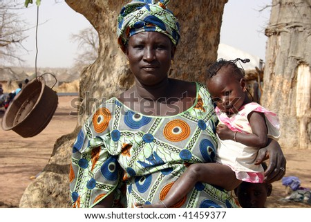 SENEGAL - FEBRUARY 13: Mother sits beside his son in Peul village near Wassadou, February 13, 2007 near Wassadou, Senegal - stock photo