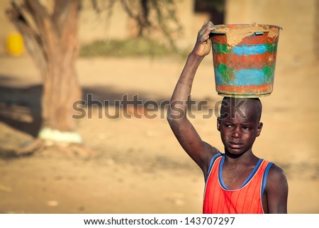 SENEGAL - MAY 4: Unidentified boy carrying clay in wooden vessel on his head, in Senegal, on May 4, 2011. Literacy rate in Senegal is only 41 percent thus, many children help at rural works. - stock photo