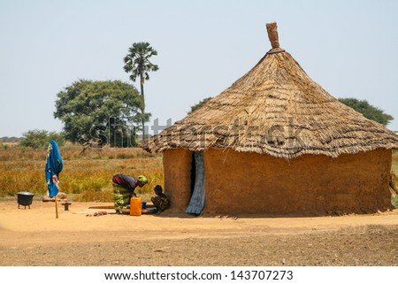 SENEGAL - MAY 4: Unidentified woman with her daughter in front of their house made of mud, in Senegal, on May 4, 2011. The house has its traditional shape with straw roof. - stock photo