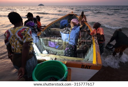 SENGA BAY - MALAWI - AUGUST 6, 2015: Unidentified fishermen and market women trading fish on August 6, 2015 in Senga Bay, Malawi - stock photo