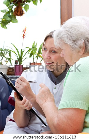 Senior adult and female nurse sit together and write data - stock photo