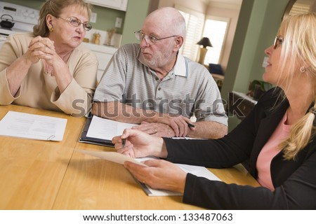 Senior Adult Couple Going Over Papers in Their Home with Agent. - stock photo