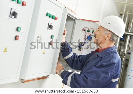 senior adult electrician builder engineer testing equipment in fuse box - stock photo