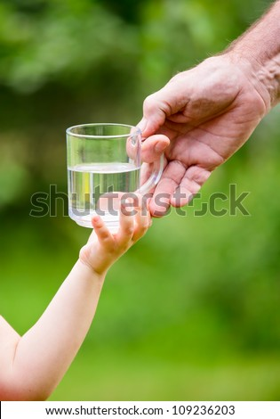 Senior adult giving mug of water to little girl outdoors - stock photo