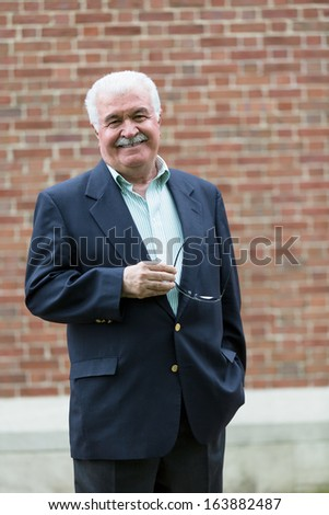 Senior adult looking at you smiling and confidingly while holding his glasses, in-front of red brick wall - stock photo