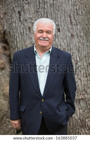 Senior adult looking at you smiling and satisfactorily in-front of huge tree trunk - stock photo