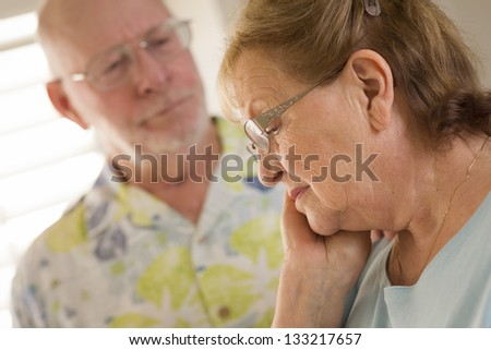 Senior Adult Man Consoles Sad Senior Adult Female. - stock photo
