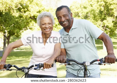 Senior African American Couple Cycling In Park - stock photo