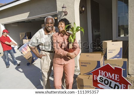 Senior African American couple moving to their new house - stock photo