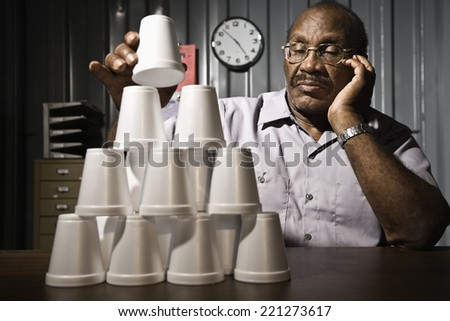 Senior African American male worker stacking cups - stock photo